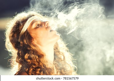 Beautiful free hippie girl blowing smoke. High, stoned, relax - Vintage effect photo