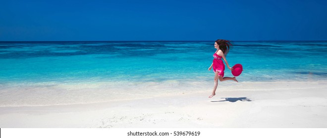 Beautiful free young woman jumping on the exotic sea, happy brunette girl in pink dress running on tropical beach with white sand. Enjoyment. Lifestyle. Freedom. Travel.