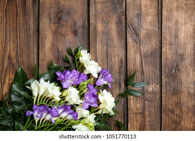 Beautiful freesia bouquet on wooden background