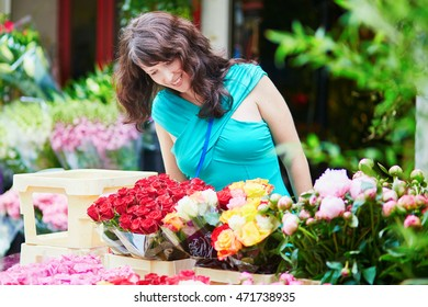 Beautiful French woman choosing flowers on a Parisian local market