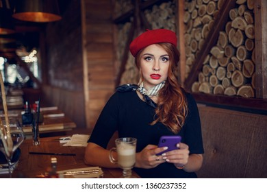 Beautiful french woman in a red cap using her mobile phone.