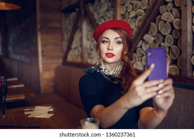 Beautiful french woman using her mobile phone and taking picture
