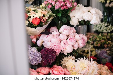 Beautiful fresh blossoming flowers in the florist shop: peonies, dahlias, roses, hydrangea  on the shelve in the florist fridge