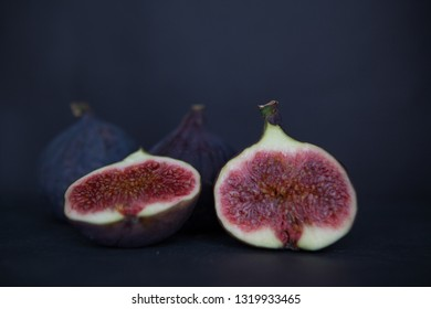 Beautiful fresh blue violet figs on dark stone background with empty copyspace close up vie from above.