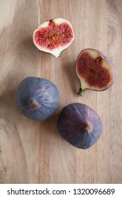 Beautiful fresh blue violet figs on a wooden cutting board background with empty copyspace close up vie from above.