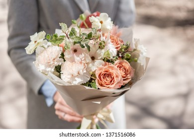 beautiful fresh cut bouquet of mixed flowers in woman hand. the work of the florist at a flower shop. Delicate Pastel tones color