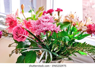Beautiful fresh cut pink flowers bouquet with green leaves in glass vase near window light in bright living room. Mother's Day, Spring blooms, birthday, anniversary and colourful life background.