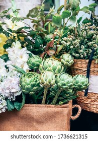 Beautiful fresh decorative green artichokes and other flowers in small florist shop. Modern style flowers arrangement in lifestyle natural light composition. Small business. Mobile photo
