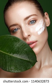 Beautiful fresh girl with cosmetic cream on the face, natural make-up and green leaves. Beauty face. Photo taken in the studio.