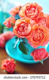 Beautiful fresh roses in a blue cup on a table.