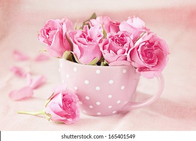 Beautiful fresh roses in a  cup on a pink background
