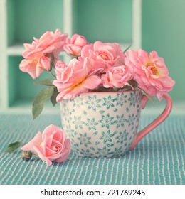 Beautiful fresh roses in a porcelain cup on a green background .