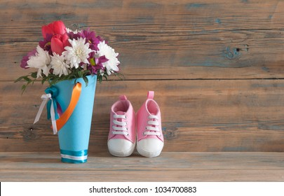 Beautiful fresh spring flowers and children's shoes on a wooden background. Baby waiting concept