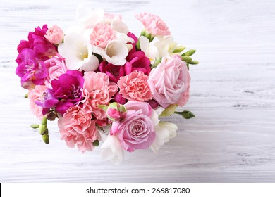 Beautiful fresh spring flowers on wooden table, top view