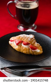 Beautiful Fresh Strawberry Croissant with Cream and Coffee on Velvet Red Table Top Plated and Ready to eat.