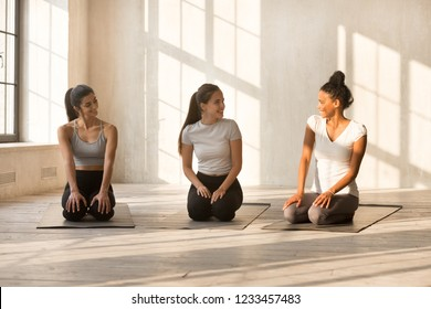 Beautiful friendly diverse young women wearing sport bra and leggings talking during workout sitting on yoga mats, best friends having pleasant conversation. Friendship and healthy lifestyle concept
