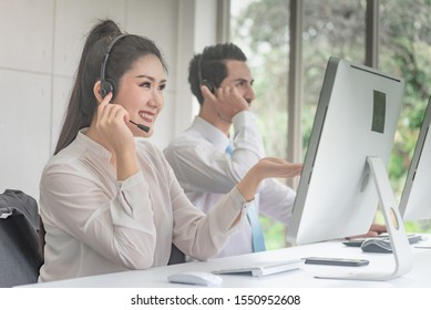 Beautiful  friendly smiling  confidence customer service support agent with headsets working with service mind and commitment at a call centre workplace.