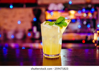 beautiful frozen cocktail glass with ice, mint and pineapple on a dark wooden bar counter, bokeh bright background