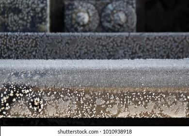Beautiful frozen metal rail fragment in winter close-up