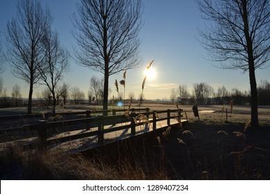 beautiful frozen rural landscape park winter scene blue sky sun bridge view