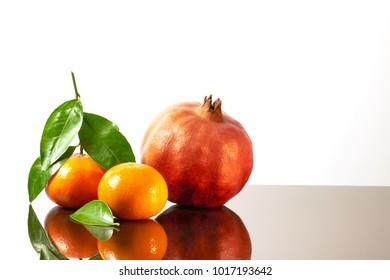 Beautiful fruits citrus family, clementines, tangerine, pomegranate and lemon on white shine background