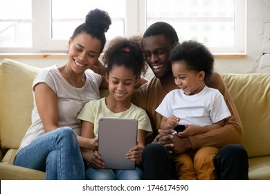 Beautiful full African family spend free time using tablet device watching cartoon educational app for kids enjoy on-line services making videocall chatting with relatives sit on couch in living room