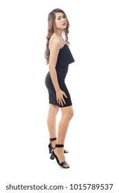 Beautiful full body Asian woman posing in black slinky top and short skirt.