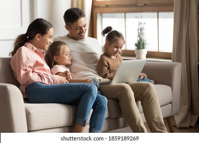 Beautiful full family with two cute daughters resting with laptop seated on sofa. Couple develop offspring watching educational online tv, buy goods on internet, have fun use modern technology concept