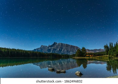 Beautiful full of stars above the Mount Rundle from Two Jack Lake at night, starry sky reflected in the water surface. Beautiful landscape in Banff National Park, Canadian Rockies, Alberta, Canada.