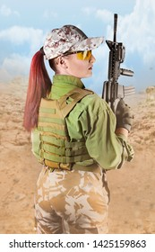 Beautiful fully equipped military soldier woman in protective armor tactical vest, camouflage pants, gloves, cap and glasses holding an automatic rifle M16, on desert background, back view.