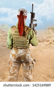 Beautiful fully equipped military soldier woman in protective armor tactical vest and camouflage pants holding an automatic rifle M16, on desert background, back view.