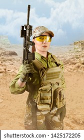 Beautiful fully equipped military soldier woman in protective armor tactical vest, camouflage pants, gloves, cap and glasses holding an automatic rifle M16, on desert background.