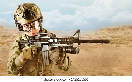 Beautiful fully equipped military soldier woman aiming at the enemy with automatic rifle M16 on desert background.