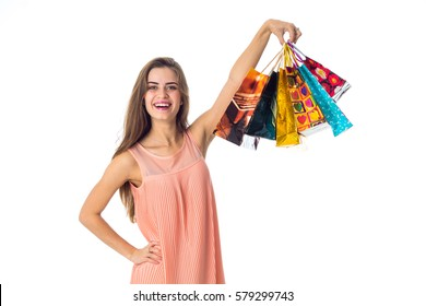 beautiful fun girl raised high in a lot of different gift packages hand isolated on white background