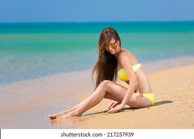 beautiful fun and joy brunette woman in yellow bikini posing  tropical  blue sea water has sports and tan body