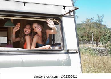 Schöne spaßige Teenager Mädchen Freunde reisen zusammen in Motor Wohnwagen auf der Sommerlandreise, lächeln, winkt zum Abschied, Abfahrt. Touristen Abenteuer Freizeit Erholung Lifestyle.