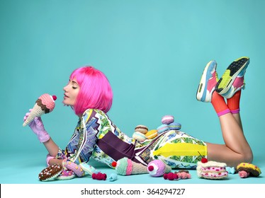 Beautiful funky fashion cheerful woman in hot pink party wig eating fake ice cream and sweet candy cakes candies on a mint background