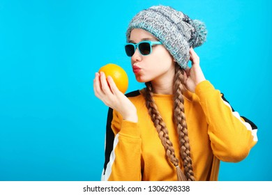 Beautiful funny caucasian girl in winter hat with bright orange on blue background.