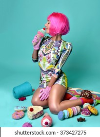 Beautiful funny fashion cheerful woman in hot pink party wig eating fake ice cream on a mint background