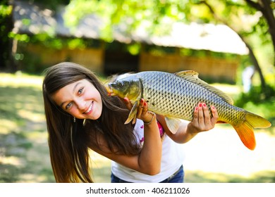 Beautiful and funny fisher woman smiling and holding big fish catch on nature background. Happy young fisherwomen, teenage girl rest outdoors and enjoy vacation in summer with fish catch.
