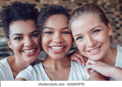 Beautiful and funny girls in white T-shirts makes selfie. Two afro-americans and one european.
