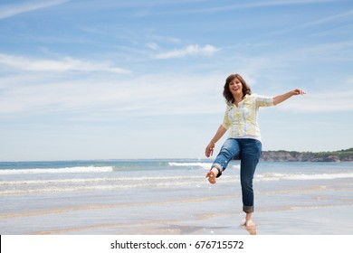 Beautiful and funny middle aged woman splashing water with foot on the seashore
