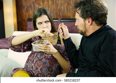 beautiful and funny pregnant woman fighting with spoon with her husband to protect her chocolate ice cream. she is having strong cravings