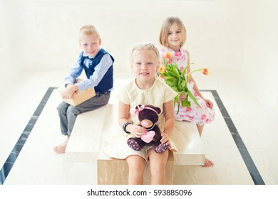 Beautiful funny toddler girl sitting in room laugh. Guests children give her a present and bouquet of tulips, ready to celebrate birthday party, or Easter holidays
