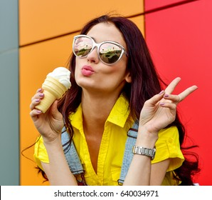 Beautiful  funny young hipster teen girl eating ice cream cone. laughs happy. Bright casual wear, denim shorts. Orange  background, urban style, sunglasses