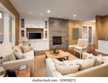 Beautiful furnished living room with fireplace and television in new luxury home.  Hardwood floors, built-ins, and stone fireplace surround make room a cozy and inviting space.