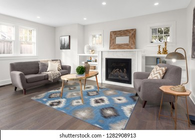 Beautiful Furnished Living Room Interior in New Home with Hardwood Floors, Fireplace, Rug, and Decor.