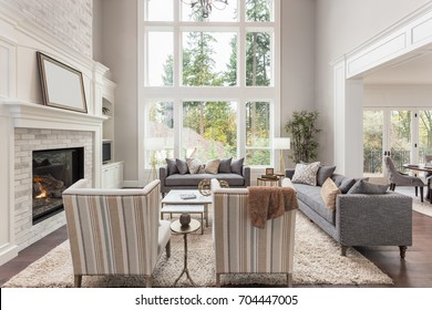 Beautiful furnished living room interior with fireplace in new luxury home. Large bank of windows allows for plenty of natural light. Includes view of eating nook.