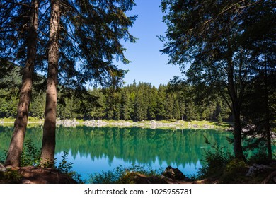 Beautiful Fusine lakes framed by nature. Trees and beautiful reflection on water surface. Tarvisio (Udine), Friuli Venezia Giulia, Italy.