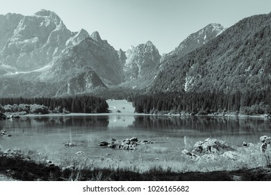 Beautiful Fusine lakes, nature, countryside, trees and mountains on background. Tarvisio (Udine), Friuli Venezia Giulia, Italy. black and white effect.